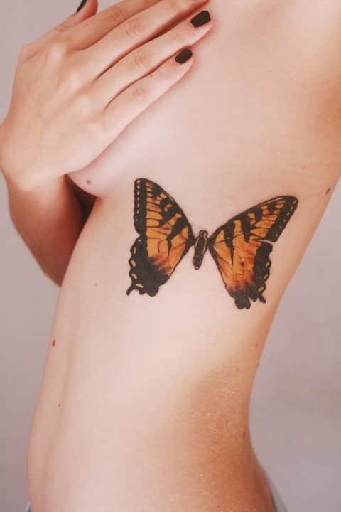 Фото тату бабочки на боку у женщины