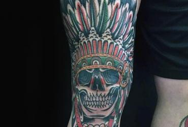 Татуировка на колене череп с перьями